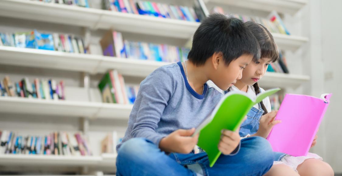 子供が図書館で本を読んでいる